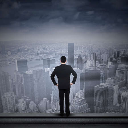 Businessman standing on the top of skyscraper and looking to the future photo