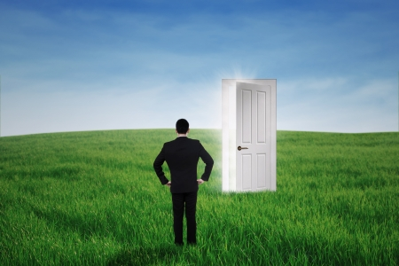 Young businessman standing at an opportunity door on the green meadow Stock Photo
