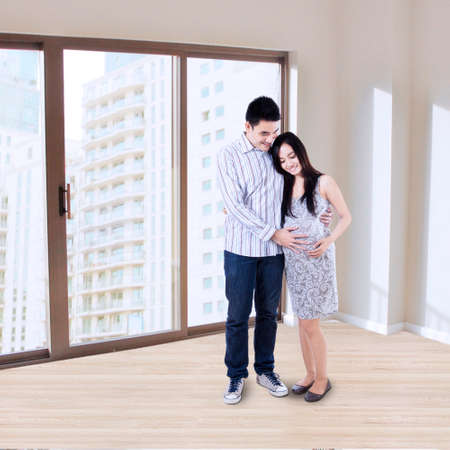 Happy young pregnant couple at new apartment photo