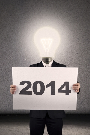 Light bulb person wearing business suit holding a 2014 billboard photo