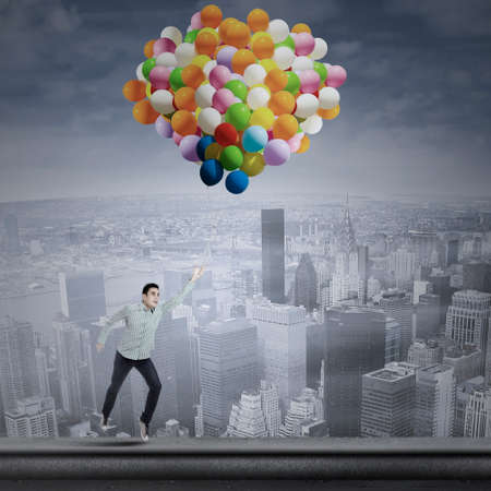 flying man: Young asian man flying with balloons over the cityscape