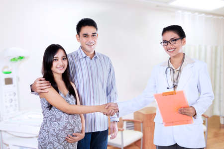 Young pregnant couple handshake with an obstetrician at hospital photo