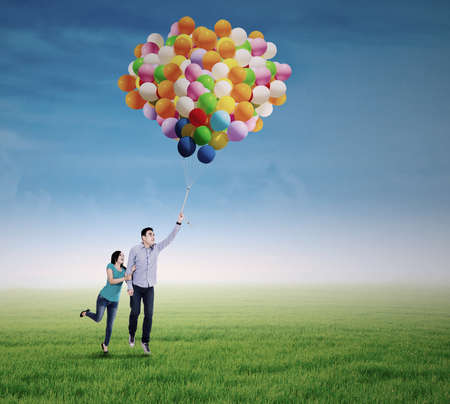 Happy young couple in love with colorful balloons on the meadow photo