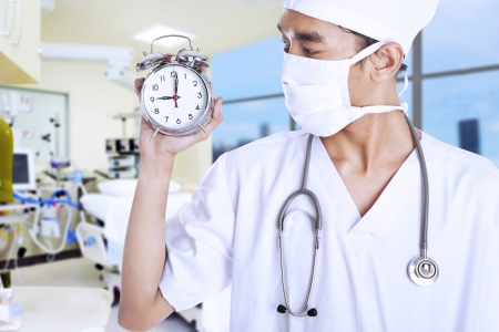 A male doctor holding an alarm clock in doctors room photo