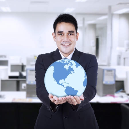 lifting globe: Asian businessman holding a globe at office Stock Photo