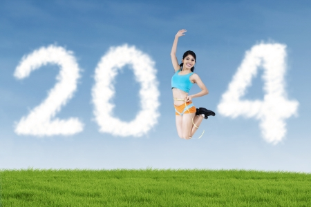 Athletic woman jumping with shaped clouds of new year 2014 outdoor photo