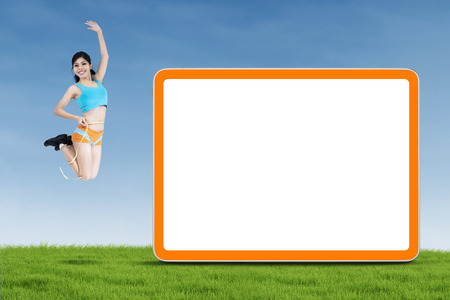 Attractive fitness woman jumping with blank board on the green field photo