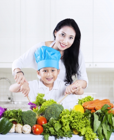 Attractive mother and her son preparing a salad at home photo