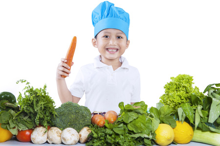 Boy with fresh vegetables isolated on white background photo