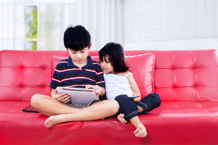 Asian brother and sister using a tablet computer on the couch photo