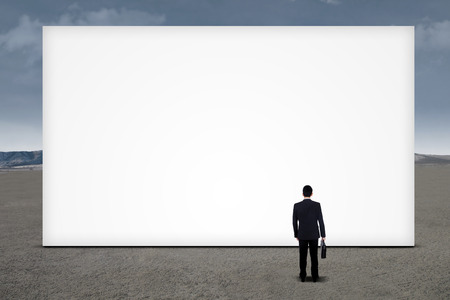Young businessman is looking at empty billboard under cloudy sky photo