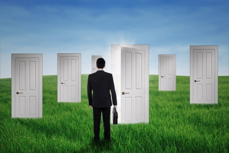 Businessman walking into opportunity doors on the green field photo