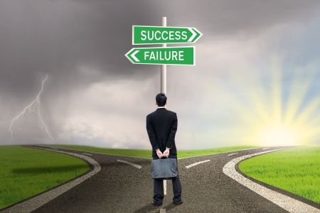 failure sign: Businessman is holding briefcase and standing on the road with a sign of success or failure Stock Photo