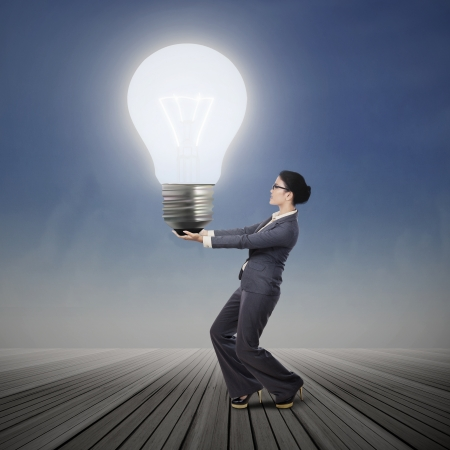 Young asian businesswoman is carrying bright light bulb outdoor