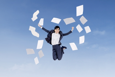 throw paper: Asian businesswoman jumping and throwing papers into air in the blue sky Stock Photo