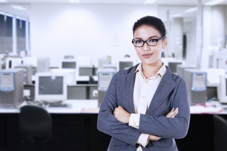 office environment: Portrait of a young businesswoman smiling, in an office environment