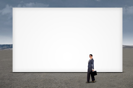 Confident businesswoman standing at empty billboard under cloudy sky photo