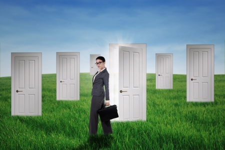 Confident businesswoman standing in front of opportunity doors on the green field photo