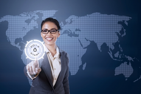 Young businesswoman touching futuristic touchscreen on blue world map background photo