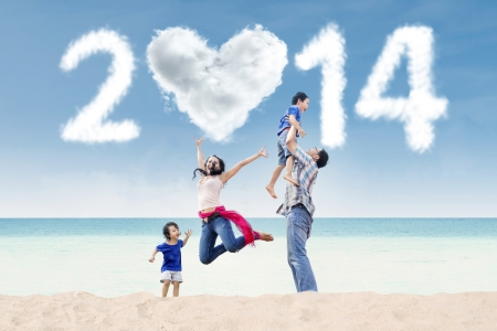 beach happy new year: Happy family having fun in the beach with heart shaped cloud of new year 2014