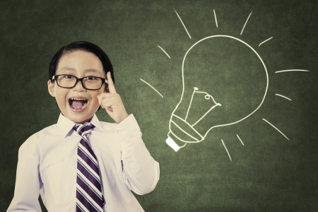 kids: Portrait of cheerful smiling school student with lightbulb picture on blackboard