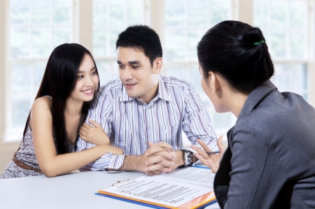Young couple meeting consultant for financial contract at home photo