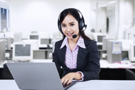 Friendly young woman operator with headset at modern office photo