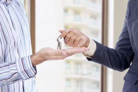 Handing of keys from one man to other at new home photo