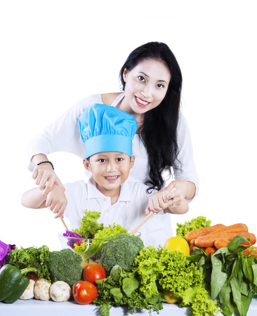 Portrait of happy mother and her son preparing a salad isolated on white background photo