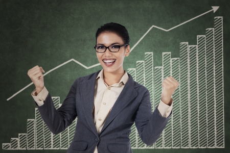 winning business woman: Happy winning business woman with arms up on growing graph background