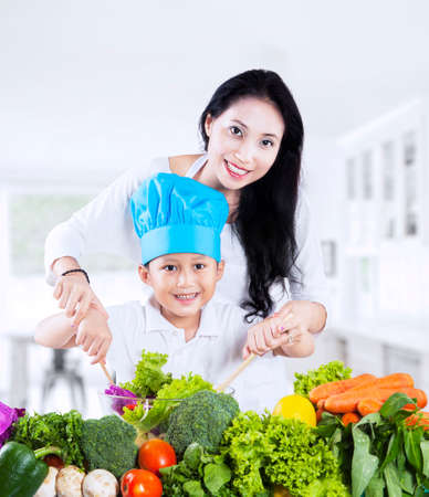 Beautiful mother and her son cooking vegetable salad in the kitchen photo