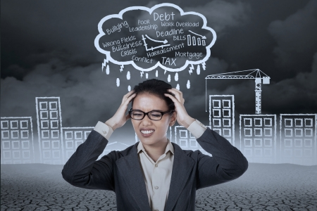 Stressed businesswoman with a headache under stormy clouds photo