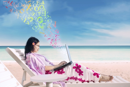 Asian woman using a laptop on the beach photo