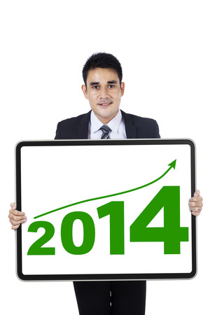 Young asian businessman showing the new year 2014 on a board photo