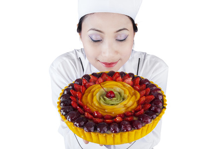 Portrait of young woman chef with fruit cake on white background photo