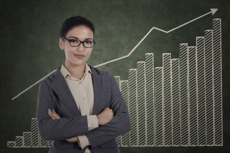 convinced: Smiling businesswoman with her arms crossed on growth graph background