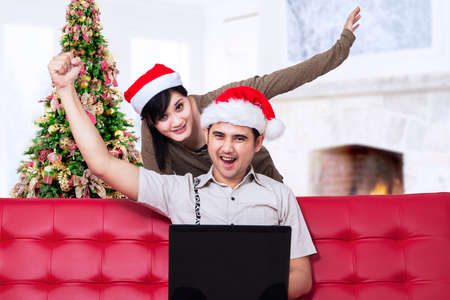 Happy asian couple buying christmas gift online at home photo