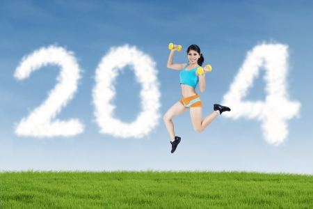 Happy fitness woman jumping with shaped clouds of new year 2014 photo