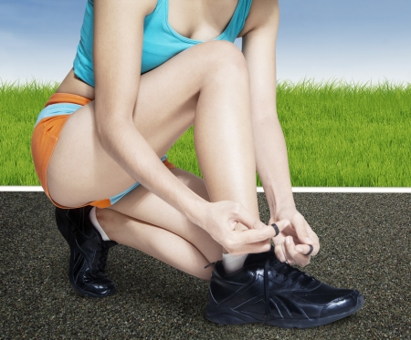 lacing sneakers: Fitness woman lacing her shoes before running outdoors