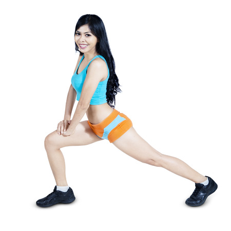 female muscle: Fitness woman stretching her leg - isolated on white background Stock Photo