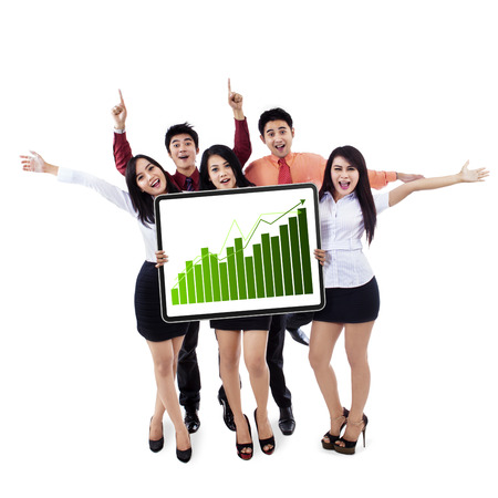Happy business team showing a growing graph isolated on white background photo
