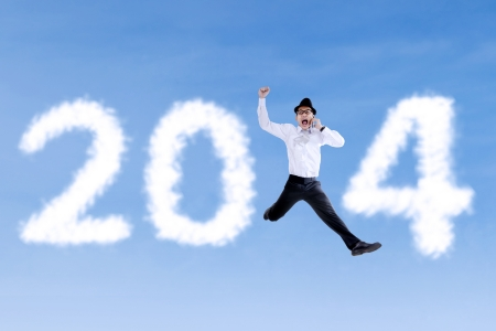 Happy businessman jumping with clouds of 2014 and using a telephone photo
