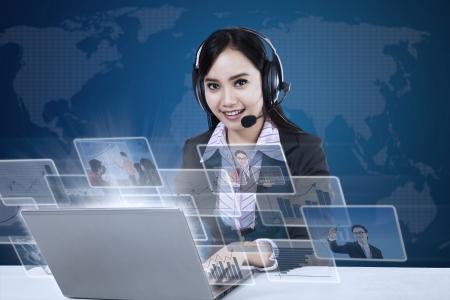 Empresaria feliz con interfaz fotos en frente de la computadora portátil en el mapa del mundo de fondo