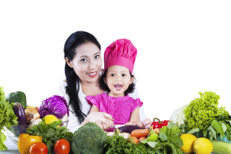 Happy mother and her daughter preparing a salad isolated on white background photo