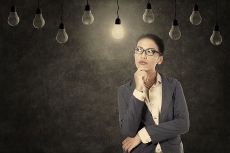 Asian businesswoman positive thinking under lit light bulb photo