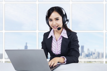 Smiling young woman operator with headset at office photo