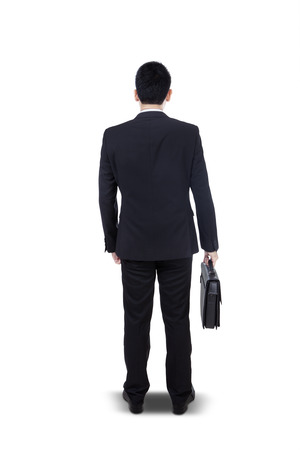 Back view of a young businessman standing with briefcase isolated on white background photo