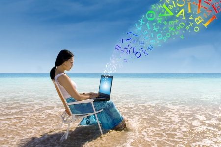 Young woman working with a laptop computer at the beach photo