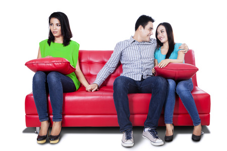 Beautiful young woman holding hands with man sitting near his girlfriend