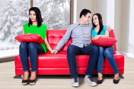 cheating woman: A woman holding hand with man sitting near his girlfriend Stock Photo